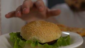 Beleibtes männliches Zögern, Burger vom Kühlschrank nachts, Willenskraftwahl zu nehmen stock video
