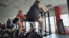 Beleibtes weibliches Arbeiten an gesundem Körper in der Turnhalle, pralle Frau, die einen Hometrainer reitet stock video