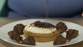 Beleibtes weibliches, Bonbons und Schokoladen mit Karamellbelagsabschluß oben reich bedeckend stock video footage