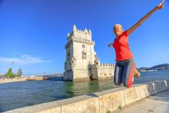 Belem Tower jumping. Happy blonde caucasian woman jumping at Belem Tower, Unesco Heritage and symbol of Lisbon, in Belem District, Tagus River. Lifestyle Stock Image