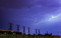 Beleuchten über Stromleitungen nachts Stockfotos