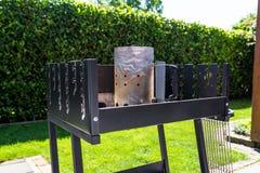 Beleuchten des Hauptgrills mit der Kohle, stehend auf einem Hausgarten auf dem Pflasterstein stockbild