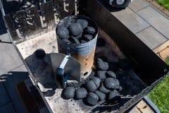 Beleuchten des Hauptgrills mit der Kohle, stehend auf einem Hausgarten auf dem Pflasterstein stockfotografie