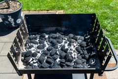Beleuchten des Hauptgrills mit der Kohle, stehend auf einem Hausgarten auf dem Pflasterstein lizenzfreie stockfotos