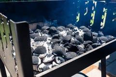 Beleuchten des Hauptgrills mit der Kohle, stehend auf einem Hausgarten auf dem Pflasterstein lizenzfreies stockbild