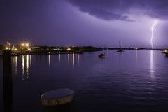 Beleuchten des Streiks über Hafen mit purpurrotem Himmel Stockfoto