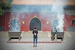 Beleuchten Sie Ihr Räucherstäbchen in Lama Temple lizenzfreie stockfotografie
