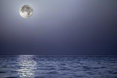 Beleuchten Sie vom Mond, der vor einem ruhigen blauen Meer sich reflektiert Stockbilder