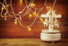 Beleuchtet weiße Karussellpferde der alten Weinlese mit Girlandengold auf Holztisch Retro- gefiltertes Bild Lizenzfreie Stockbilder