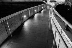 Beleuchtete Bahn nachts mit Backsteinmauern und Handlauf Lizenzfreies Stockfoto