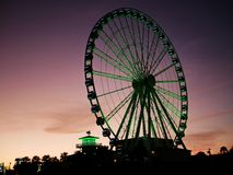 Beleuchteter Ferris Wheel auf dem Strand an der Dämmerung stockbild
