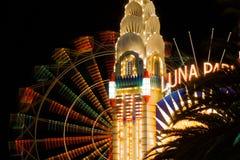 Beleuchteter Turm mit bunter Riesenradunschärfe nachts Stockbild