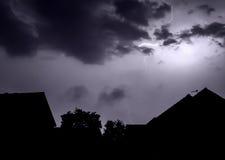 Beleuchtungsbolzen über Häusern Stockbild