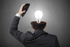 Beleuchtungslampe innerhalb des Geschäftsmannkopfes im grauen konkreten backgroun Stockfoto