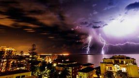 Beleuchtungssturm über einer surfy Strandstadt nachts stockfotografie