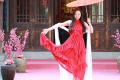 A beleza chinesa despreocupada está dançando no vestido vermelho fotografia de stock royalty free
