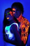 A beleza criativa do homem e da mulher da luz de néon compõe a arte corporal Fotografia de Stock
