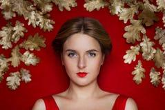 Beleza da juventude dourada em um fundo vermelho com luxo dourado Fotografia de Stock Royalty Free