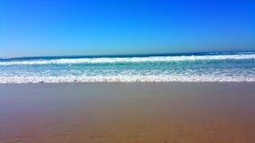 A beleza das cores da água, da areia e do pé pisa lavando afastado Fotografia de Stock