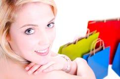 A beleza disparou de uma mulher lindo nova que olha sobre seus sacos de compras do whit do ombro na terra Foto de Stock