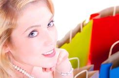 A beleza disparou de uma mulher lindo nova que olha sobre seus sacos de compras do whit do ombro na terra Imagens de Stock Royalty Free