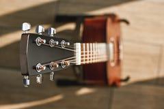 Beleza do instrumento musical Foto criativa da vista superior da guitarra acústica marrom com foco no headstock contra imagem de stock