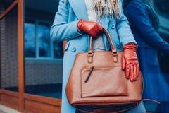 Beleza e fôrma Revestimento vestindo à moda e luvas da mulher elegante, guardando a bolsa marrom do saco imagem de stock royalty free
