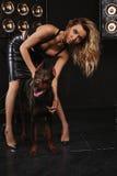 Beleza e fôrma A mulher com cabelo encaracolado lindo abraça o Doberman Fundo escuro, o ao lado da menina com um cão Fotografia de Stock Royalty Free