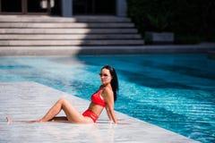 A beleza moreno de sorriso nova de arrelia da mulher com biquini vermelho descansa a colocação no verão de apreciação de mármore  Foto de Stock Royalty Free