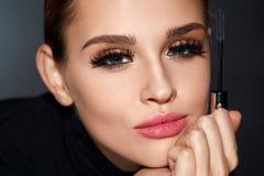 beleza Mulher com a escova bonita da cara e do rímel à disposição Fotos de Stock