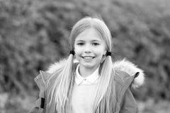 Beleza, olhar, penteado Menina com sorriso do rabo de cavalo do cabelo louro na paisagem natural Conceito feliz da infância Crian foto de stock