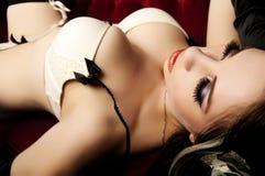 Beleza 'sexy' no sofá vermelho Imagens de Stock Royalty Free