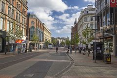 Belfast city centre daytime cityscape. Bus lane, sidewalks and shops downtown Belfast on a sunny blus sky day stock image