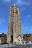 The belfry of the Church of Saint Eloi in Dunkirk, France. Dunkirk, France - May 31, 2017: Tourists walk around the belfry, originally the western tower of the Royalty Free Stock Photography