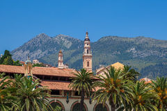 Belfry among houses and palms in Menton, France. Stock Photos