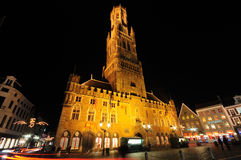 Belfry Tower at night. Night picture at Christmas showing the Belfry Tower in Markt Square, Bruges, with typical illuminated Belgium architecture buildings, bars Royalty Free Stock Photography