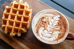 Belgain waffle. And a cup of cappuccino on a wooden Stock Photos