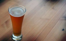 Belgian beer glass on wooden table. Royalty Free Stock Photos