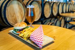 Belgian cheeseburger, French fries and beer with blurred wooden barrels in background stock images