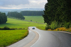 Belgian East Cantons. Car on winding road in a rainy Ardennes Landscape near Waimes in the Belgian East Cantons Stock Photo