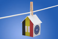 Belgian end EU flag on paper house. Concept - Belgian and EU flag painted on a paper house hanging on a rope Stock Image