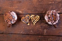 Belgian heart shaped waffle with hot chocolate with marshmallow on wooden background. Stock Image