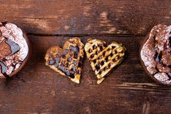 Belgian heart shaped waffle with hot chocolate with marshmallow on wooden background. Stock Photos