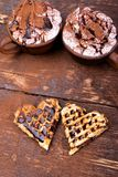 Belgian heart shaped waffle with hot chocolate with marshmallow on wooden background. Royalty Free Stock Images