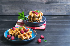 Belgian lush round waffles with fresh raspberries. Twigs and leaves mty in a blue ceramic plate and bowl on dark wooden background, empty space for your text Stock Photos