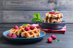 Belgian lush round waffles with fresh raspberries. Twigs and leaves mty in a blue ceramic plate and bowl on dark wooden background, empty space for your text Stock Photo