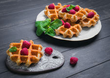 Belgian lush round waffles with fresh raspberries. Twigs and leaves mty in a white plate and ceramic board with lace pattern on dark wooden background, empty Stock Photo