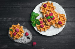 Belgian lush round waffles with fresh raspberries. Twigs and leaves mty in a white plate and ceramic board with lace pattern on dark wooden background, empty Stock Photos