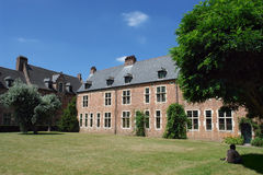 Belgian medieval campus. Medieval campus in the Louvain (Belgium) beguinage. Medieval houses with a court, trees, a lawn and a meditating student Stock Photos