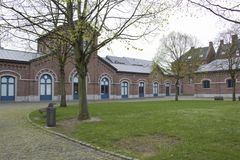 Belgian old mining site turned into museum. Grass. Flowers. Cloudy day. Trees stock photography